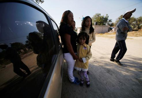 Residents look on as they wait for news near an area where dangerous radioactive medical material was found on a truck, in the town of Hueypoxtla, near Mexico City December 5, 2013. Mexican police have found dangerous radioactive medical material stolen by thieves that the United Nations said could provide an ingredient for a