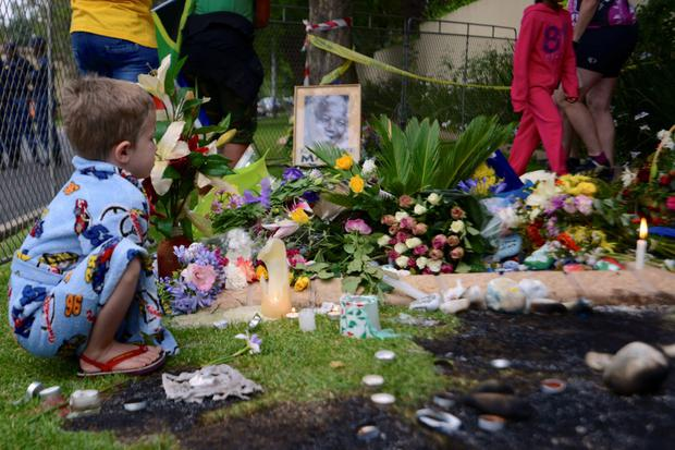 A boy pauses at a shrine outside the home of former South African President Nelson Mandela in Johannesburg December 6, 2013.