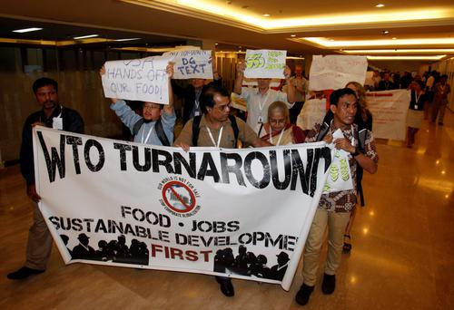 Protesters march through the meeting venue of the ninth World Trade Organization (WTO) Ministerial Conference where concluding talks are taking place, in Nusa Dua