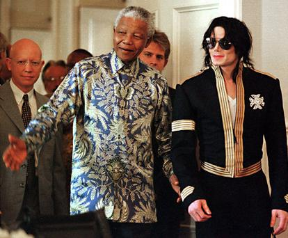 1999 Mandela and Michael Jackson arrive at a news conference in Cape Town, where Jackson announced dates for two concerts with profits to go to various funds including the Nelson Mandela Children's Fund.