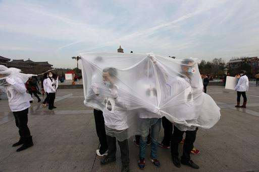 College students wearing masks pose with a plastic bag during a performance art to raise awareness of air pollution