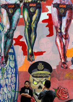 Youths take pictures in front of wall with graffiti opposing the military and depicting riot police in downtown Cairo