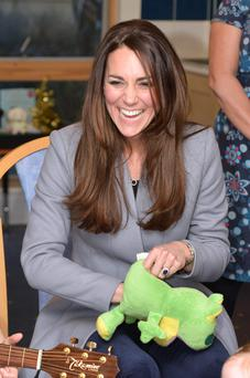 The Duchess Of Cambridge plays with a frog puppet as she visits Shooting Star House children's hospice in England