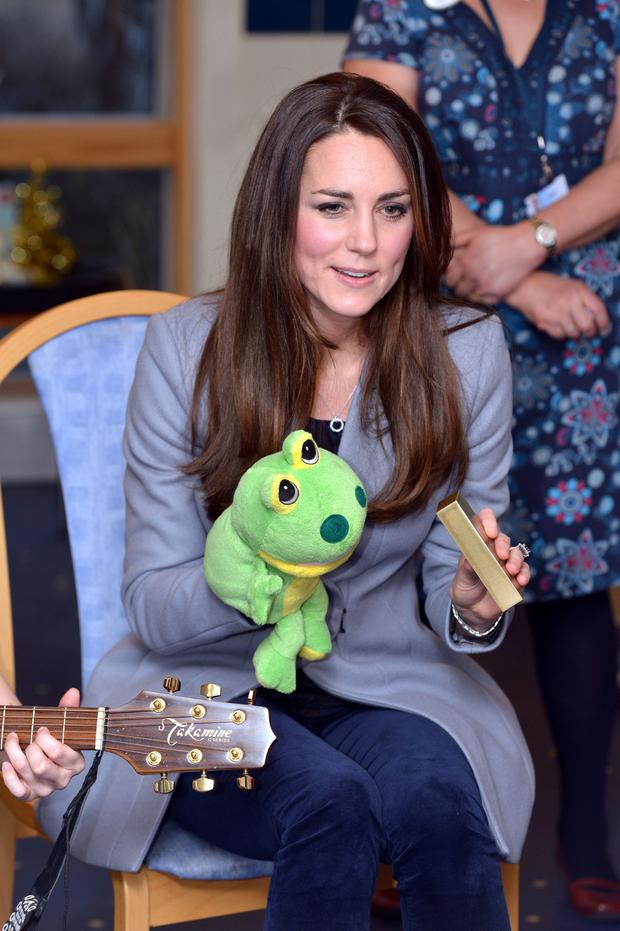 Kate Middleton plays with a frog puppet as she visits Shooting Star House children's hospice in England