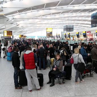 Passengers queue to check in and to re-book tickets at Terminal 5 of Heathrow Airport after a