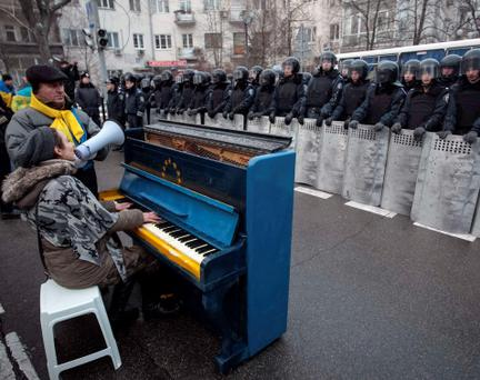 Protestors sing and play a piano decorated with EU and Ukrainian symbols as Interior Ministry members stand guard near the presidential administration building.