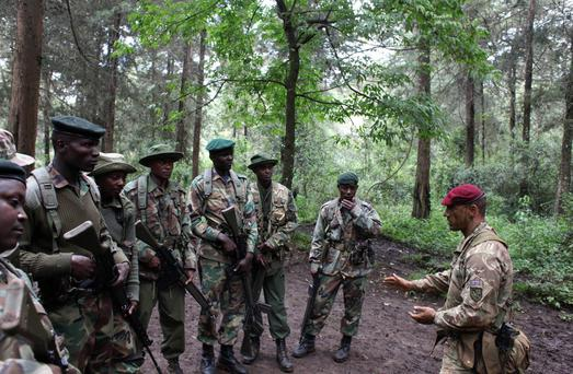 A British Army Paratrooper (R) instructs Kenyan rangers during a training course against poaching and logging near Nanyuki town, some 200 km (124 miles) north of the capital Nairobi, December 5, 2013. To help in the fight against poaching, British Army paratroopers provided patrolling and field training to members of the Kenya Wildlife Service (KWS), Kenya Forest Service (KFS), and Mount Kenya Trust (MKT) at the foot of Mount Kenya. REUTERS/Andreea Campeanu (KENYA - Tags: SOCIETY ENVIRONMENT CRIME LAW)
