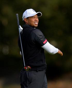 Tiger Woods drops his club as he makes his approach shot on the fifth hole during the third round of the Northwestern Mutual World Challenge golf tournament at Sherwood Country Club