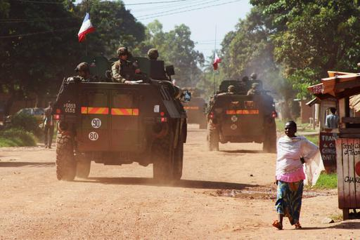 A woman walks past French soldiers on patrol in Bangui, Central African Republic