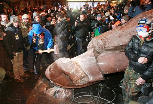 A man holds a sledgehammer as he smashes a statue of Soviet state founder Vladimir Lenin, which was toppled by protesters during a rally organized by supporters of EU integration in Kiev. Photo: Reuters