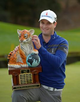 Zach Johnson scratches the head of the tiger on the trophy after winning a playoff against Tiger Woods in the final round of the Northwestern Mutual World Challenge golf tournament at Sherwood Country Club