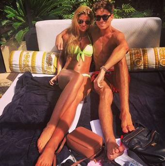 Joey shared a photo of himself and an already-bronzed Amy soaking up the sun as they relaxed poolside at the luxurious Versace hotel in Oz. (Instagram/Joey Essex)