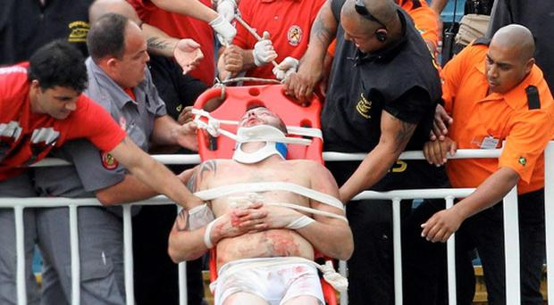 Paramedics use a stretcher to carry an injured Atletico Paranaense fan after clashes between fans of Vasco da Gama and Atletico Paranaense yesterday