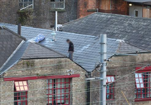 The stabbing suspect on the edge of a rooftop of a building off Store Street