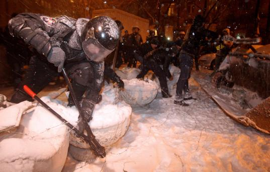 Riot police remove a barricade set up by supporters of EU integration in Kiev, December 9, 2013. Ukrainian President Viktor Yanukovich backed a call for talks with the opposition on Monday to end weeks of protests in Kiev, but tension was high with pro-Europe demonstrators barricading their protest camp in preparation for police intervention. REUTERS/Valentyn Ogirenko (UKRAINE - Tags: POLITICS CIVIL UNREST)