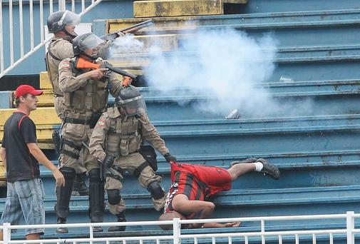 Brazilian police fire rubber bullets to quell violence during a match in the Joinville Stadium