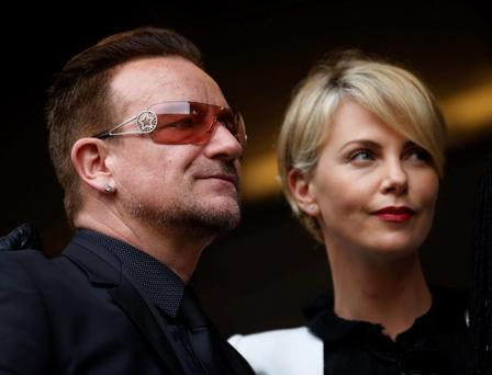 Actress Charlize Theron waits with musician Bono for the memorial service for former South African president Nelson Mandela at the FNB Stadium in Soweto near Johannesburg, Tuesday, Dec. 10, 2013. (AP Photo/Ben Curtis)