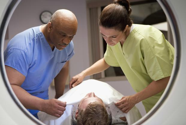 View of technicians preparing patient for MRI (stock photo)
