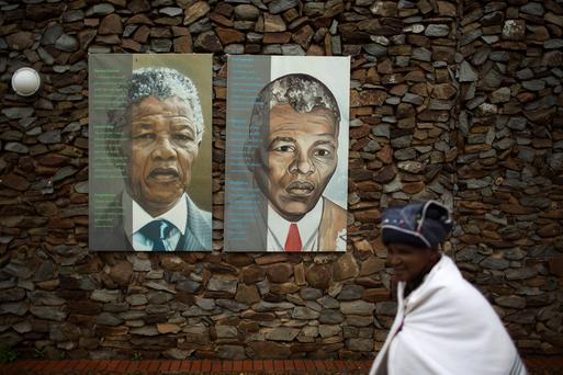 A woman walks past portraits of former South African President Nelson Mandela at the end of a memorial service in the Nelson Mandela Museum in Qunu