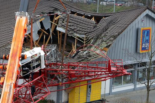 BAD HOMBURG, GERMANY - DECEMBER 11: Police and emergency rescue workers stand at the site of an accident in which a construction crane fell onto part of an Aldi supermarket on December 11, 2013 in Bad Homburg, Germany. Police report that at least one person is dead and several injured after the tip of the crane crashed down on the section of the store where customers were waiting in line at the cash registers. (Photo by Hannelore Foerster/Getty Images)