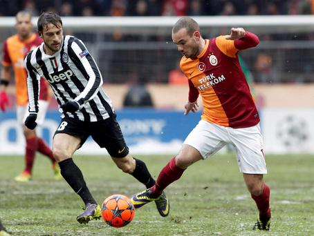 Wesley Sneijder (R) of Galatasaray challenges Claudio Marchisio of Juventus during their Champions League soccer match in Istanbul