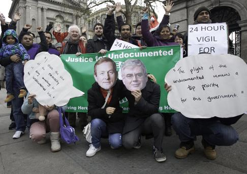 11/12/2013 Supporters of undocumented families wearing Taoiseach Enda Kenny TD & Tanaiste Eamon Gilmore TD masks during a 24 hour vigil to highlight the plight of undocumented migrants at Christmastime outside Leinster House, Dublin. Photo: Gareth Chaney Collins