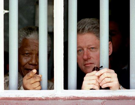 FILE - In this March 27, 1998 file photo, Nelson Mandela and former US president Bill Clinton look to the outside from Mandela's Robben Island prison cell in Cape Town, South Africa
