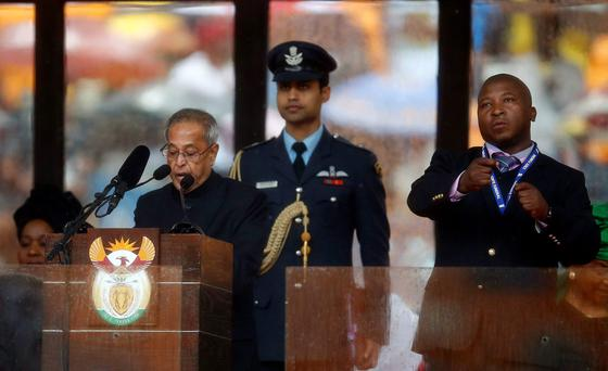 India's President Pranab Mukherjee speaks at the podium as a sign language interpreter (R) punches the air beside him during a memorial service for late South African President Nelson Mandela at the FNB soccer stadium in Johannesburg December 10, 2013.