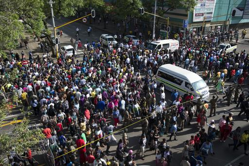 People cross a junction after watching the funeral cortege of former South African president Nelson Mandela pass along Madiba St towards Union Buildings where the anti-apartheid hero will lay in state for the second of three days on December 12, 2013 in Pretoria, South Africa.