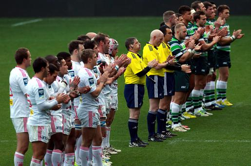 London Irish and Stade Francais participate in a minutes applause for Nelson Mandela during the Amlin Challenge Cup match at the Madejski Stadium
