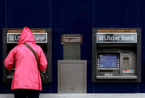 A customer uses a cash machine at a branch of the Ulster Bank
