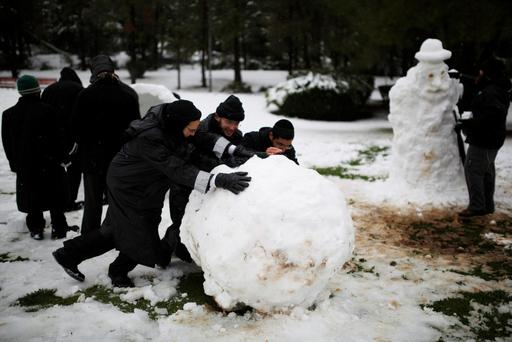 Ultra-Orthodox Jewish men roll a snowball after a snowstorm at a park during winter in Jerusalem
