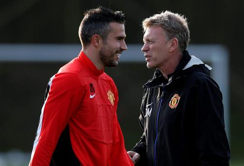 Manchester United's Robin Van Persie (L) walks past manager David Moyes during a training session