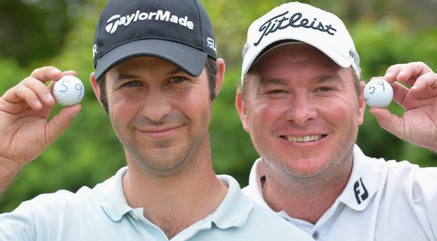 Jorge Campillo of Spain and Colin Nel of South Africa both hold their golf ball with the number 59 after they both simultaneously shot 59 during the second round of the Nelson Mandela Championship