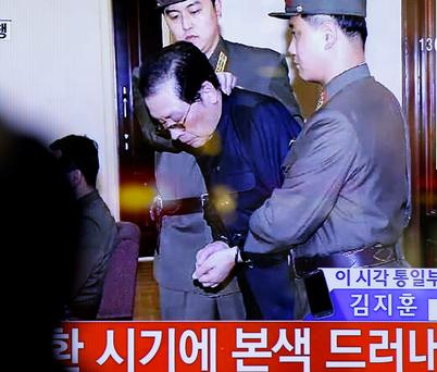 A live TV news programme showing North Korean leader Kim Jong Un's uncle Jang Song Thaek, second from right, escorted by military officers during a trial in Pyongyang, North Korea