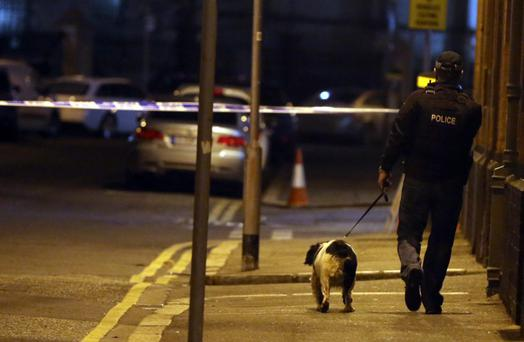 Police with a sniffer dog search the Cathedral Quarter in Belfast after a small explosion in Belfast city centre, police said the incident came after a telephone bomb warning had been made.