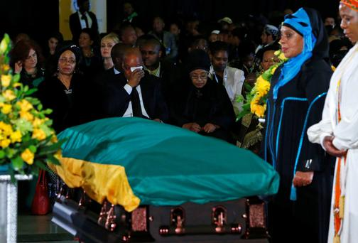 South African President Jacob Zuma (back C) wipes his tears while sitting beside Winnie Mandela (back R) and Graca Machel (back L) during a send-off ceremony for late former South African President Nelson Mandela at Waterkloof Air Force base in Pretoria