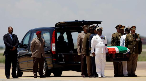 Nelson Mandela's grandson Mandla Mandela, left, watches as the casket of former South African President Nelson Mandela is taken out of a hearse following a farewell ceremony by the African National Congress at Waterkloof Air Base on the outskirts of Pretoria, South Africa, Saturday, Dec. 14, 2013. The remains of Nelson Mandela were being transferred amid pomp and ceremony to his home village for burial the next day. (AP Photo/Themba Hadebe)