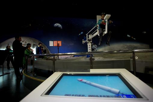 A woman tries out a moonwalker device at the China Science and Technology Museum in Beijing Saturday, Dec. 14, 2013. China will attempt the world's first soft landing of a rover on the moon in nearly four decades Saturday, the latest step in the country's ambitious space program. The Chang'e 3 lander is scheduled to touch down at 9:40 p.m. (1340 GMT; 8:40 a.m. EST) Saturday, according to state media. (AP Photo/Andy Wong)