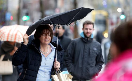 Shoppers battle the wind and rain in Dublin City centre. Photo: Gerry Mooney