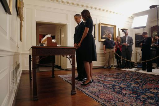 U.S. President Barack Obama and first lady Michelle Obama observe a moment of silence after lighting candles in memory of the 20 children and six school workers killed by a gunman at Sandy Hook Elementary School one year ago, in the Map Room at the White House in Washington, December 14, 2013. Obama marked the anniversary of the Newtown, Connecticut, school shootings on Saturday by calling for tighter gun control and expanded mental health care. REUTERS/Jonathan Ernst (UNITED STATES - Tags: POLITICS ANNIVERSARY)