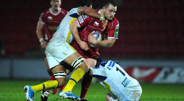 Llanelli Scarlets' Ken Owens is tackled by ASM Clermont Auvergne's Damien Chouly and Thomas Domingo