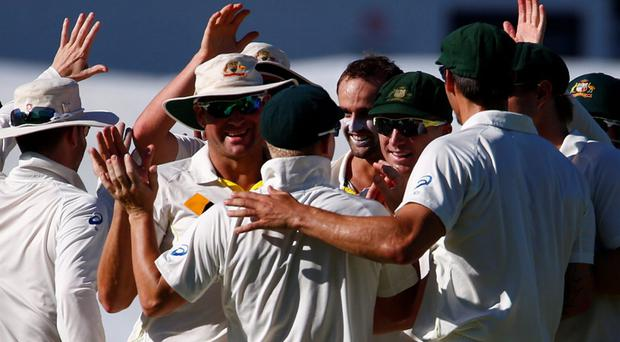 Australia's Nathan Lyon (C) celebrates with teammates taking the wicket of England's captain Alastair Cook during the second day of the third Ashes test cricket match