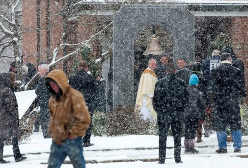People gather following mass at St. Rose church as a permanent memorial is dedicated to the victims of the Sandy Hook Elementary School shooting in Newtown, Connecticut