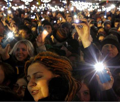 Pro-European integration protesters hold up their mobile phones during a concert in a camp at Independence Square in Kiev