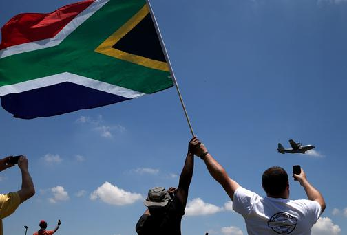 People wave a South African flag as they watch a South African Air Force C-130 carrying the casket of former South African President Nelson Mandela