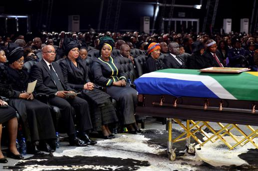 South Africa's President Jacob Zuma (2nd L), the ex-wife of former South African President Nelson Mandela, Winnie Mandela (L), and the widow of Mandela, Graca Machel (3rd L), sit by the coffin of Mandela during his funeral ceremony