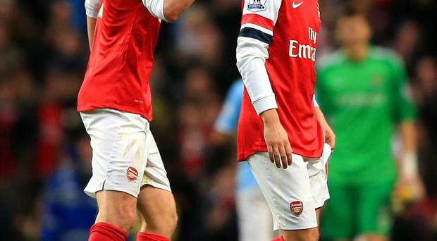 Per Mertesacker of Arsenal has words with Mesut Ozil after he snubs Arsenal fans after the game yesterday
