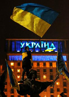 A pro-European integration protestor waves a Ukranian flag on top of a statue in Independence Square in Kiev December 15, 2013. Thousands massed on Sunday for a rally against President Viktor Yanukovich just days before he heads for a meeting at the Kremlin which the opposition fears will slam the door on integration with the European mainstream. REUTERS/Alexander Demianchuk (UKRAINE - Tags: POLITICS CIVIL UNREST)
