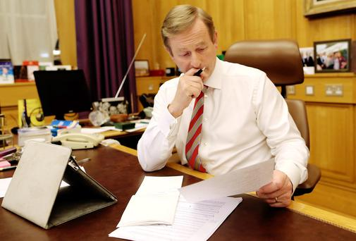 Enda Kenny preparing his address at his office desk in Government Buildings